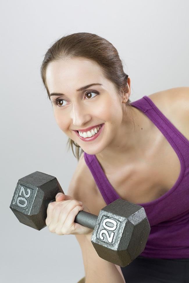 Aquí vemos a una mujer haciendo deporte de fuerza y siguiendo una dieta