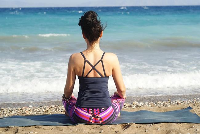 Realizando yoga en la playa uno de los grandes métodos para calmar la ansiedad