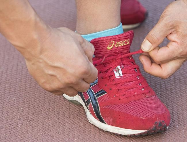 Un corredor se amarra la zapatilla después de correr